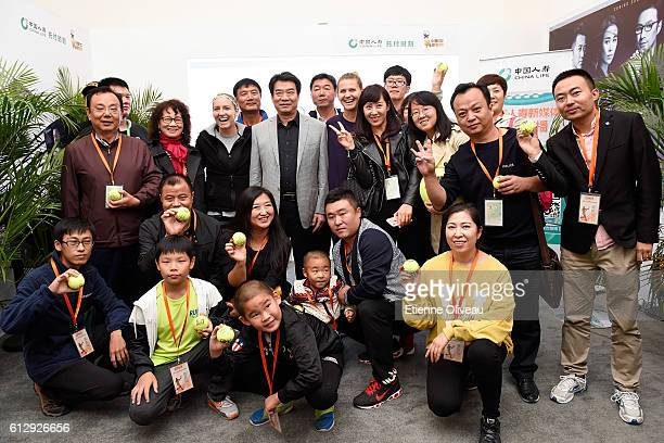 Bethanie Mattek-Sands of United States and Lucie Safarova of Czech Republic pose for a picture with staff members at the China Life Booth on day six...