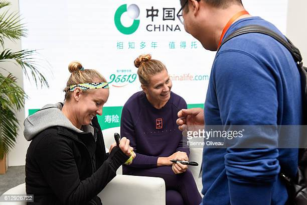 Bethanie Mattek-Sands of United States and Lucie Safarova of Czech Republic sign autographs at the China Life Booth on day six of the 2016 China Open...