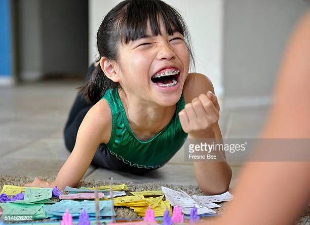 Bethany Wong who was born with a deformed right arm lets loose with a laugh as she plays a board game with sister Bayley