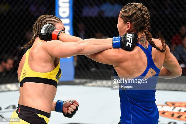 Bethe Correia of Brazil and Jessica Eye exchange punches in their women's bantamweight bout during the UFC 203 event at Quicken Loans Arena on...