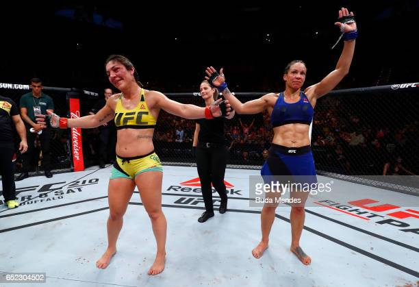 Bethe Correia of Brazil and Marion Reneau react after fighting to a draw in their women's bantamweight bout during the UFC Fight Night event at CFO...