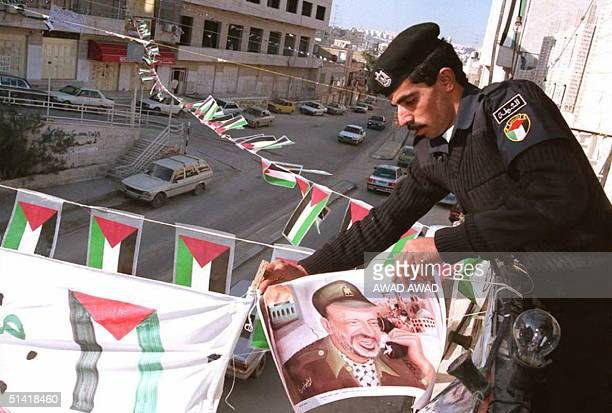 One of the very first Palestinian policemen who arrived to the West Bank town of Bethlehem hangs up a picture of Palestinian leader Yasser Arafat 20...
