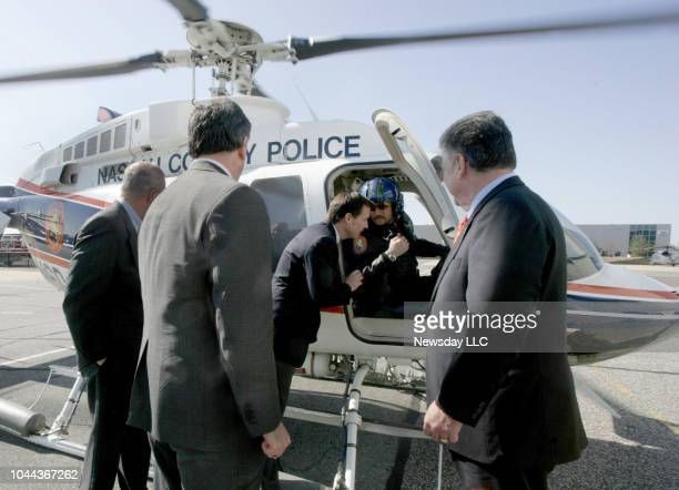 Nassau County Executive Tom Suozzi leans in to talk to police officer/helicopter pilot Eric Reusch in Bethpage NY on March 25 2008 From left Police...