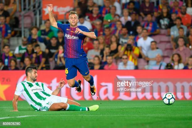Betis' forward Alex Alegria vies with Barcelona's forward Gerard Deulofeu during the Spanish league footbal match FC Barcelona vs Real Betis at the...