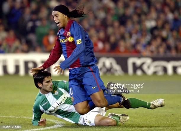 Betis's Juanito Gutierrez tackles Barcelona's Brazilian Ronaldo de Assis Moreira during a Spanish league football match at the Ruiz de Lopera stadium...