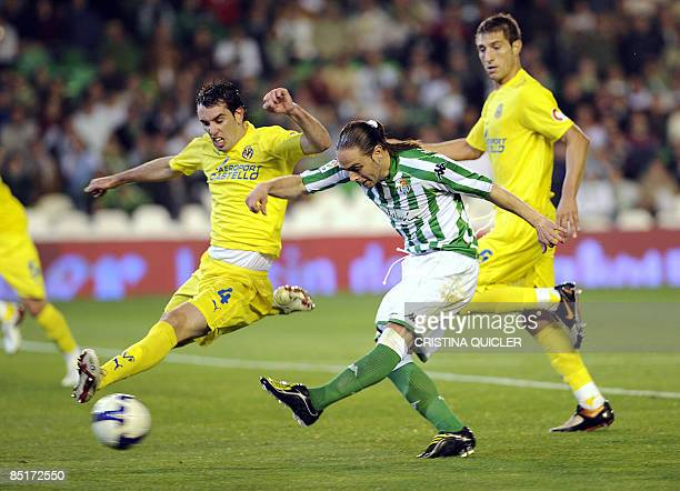 Betis's Sergio Garcia shoots and scores next to Villarreal's Diego Godin and Jose Joaquin Moreno during their Spanish league football match at Ruiz...