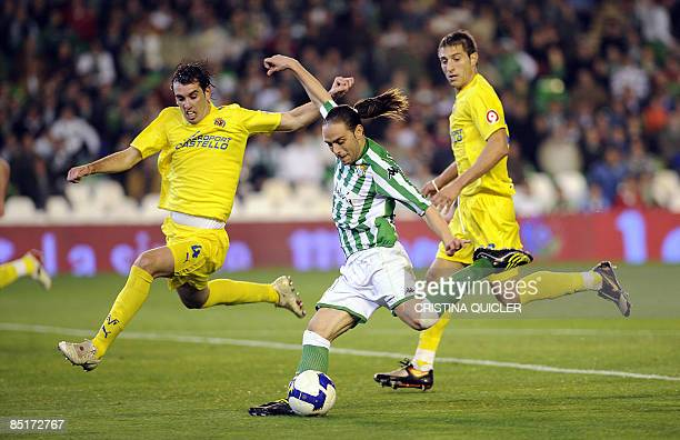Betis's Sergio Garcia shots and scores next to Villarreal's Diego Godin and Jose Joaquin Moreno during their Spanish league football match at Ruiz de...