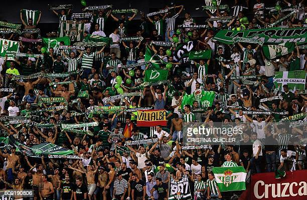 Betis's supporters brandish their team scarfs during the Spanish league football match Sevilla FC vs Real Betis at the Ramon Sanchez Pizjuan stadium...