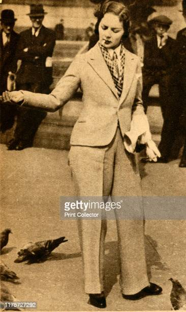A betrousered lady feeding pigeons in Trafalgar Square' 1933 Smoking woman wearing a trousersuit in central London This style of dress became...