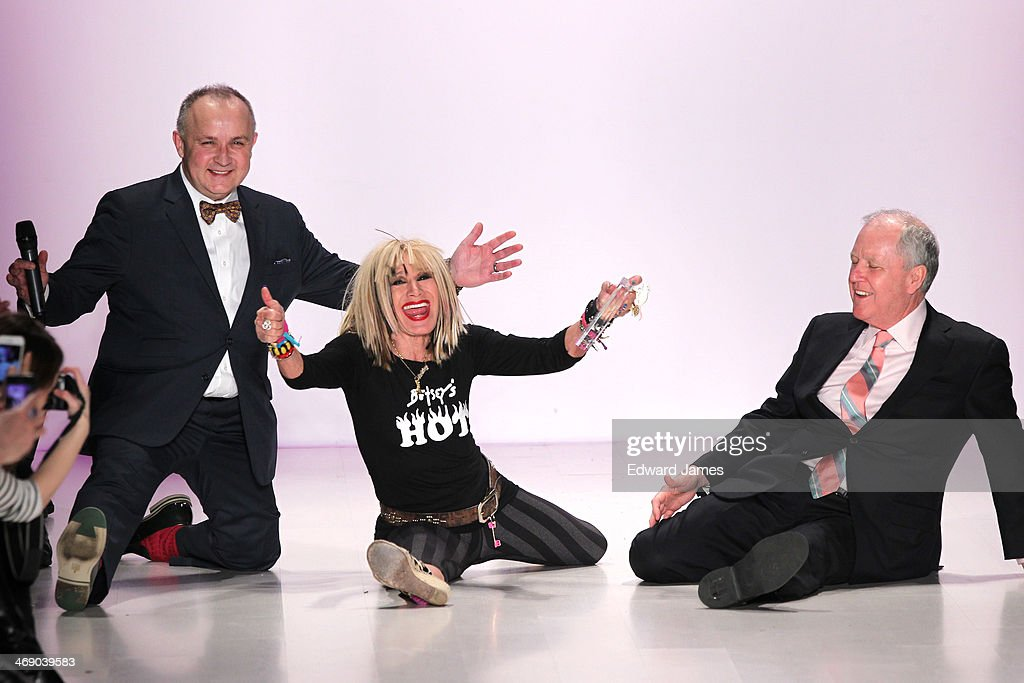 Betsey Johnson does the splits on the runway with the director's from Marist College at Betsey Johnson Reprise during Mercedes-Benz Fashion Week Fall 2014 at The Salon at Lincoln Center on February 12, 2014 in New York City.