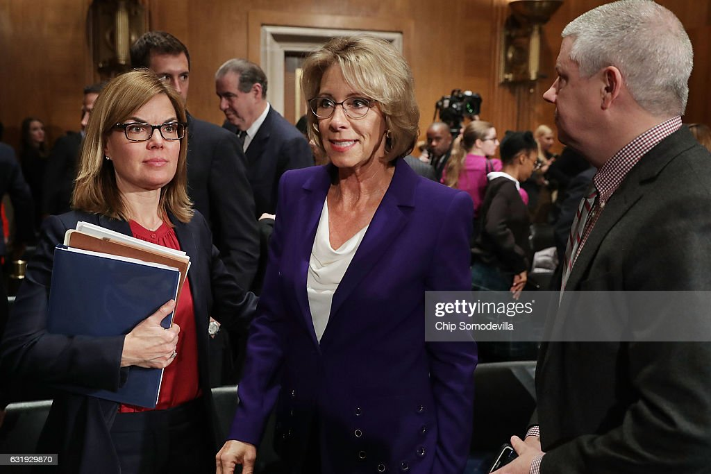 Betsy DeVos (C), President-elect Donald Trump's pick to be the next Secretary of Education, leaves at the conclusion of her confirmation hearing before the Senate Health, Education, Labor and Pensions Committee in the Dirksen Senate Office Building on Capitol Hill January 17, 2017 in Washington, DC. DeVos is known for her advocacy of school choice and education voucher programs and is a long-time leader of the Republican Party in Michigan.