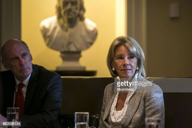 Betsy DeVos US secretary of education right and Dan Coats director of national intelligence listen as US President Donald Trump not pictured speaks...