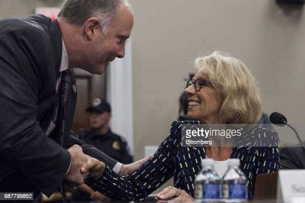 Betsy DeVos US secretary of education right shakes hands with Representative John Moolenaar a Republican from Mississippi before a House...