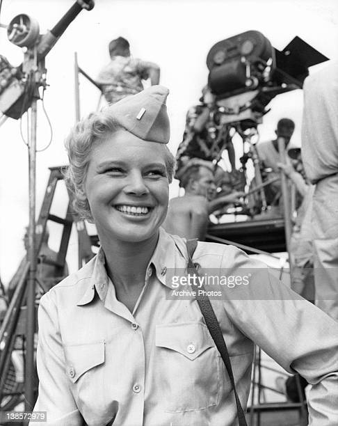 Betsy Palmer in a military uniform smiling with a filming crew behind her in a scene from the film 'Mister Roberts' 1955