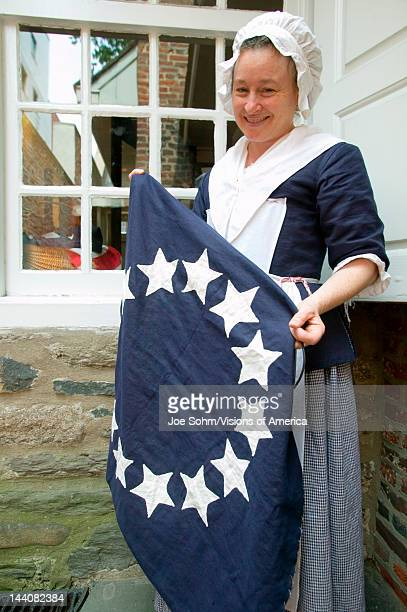 Betsy Ross actor holds colonial flag in The Betsy Ross House on East Third Street Philadelphia Pennsylvania