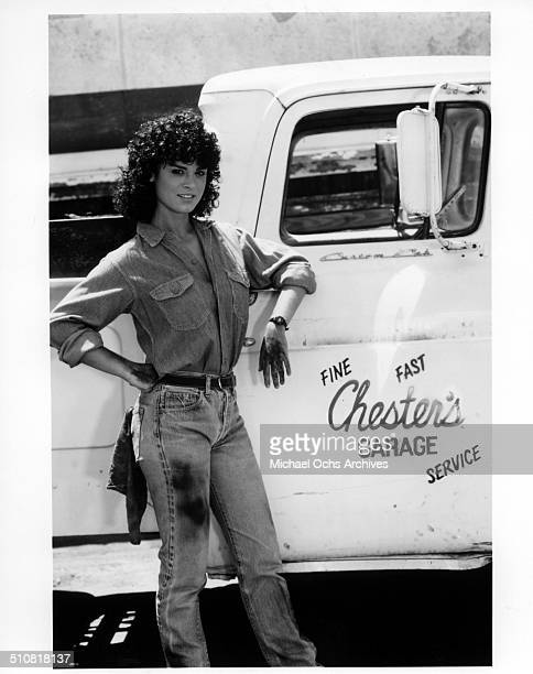 Betsy Russell poses next to a pickup truck for the movie Tomboy circa 1985