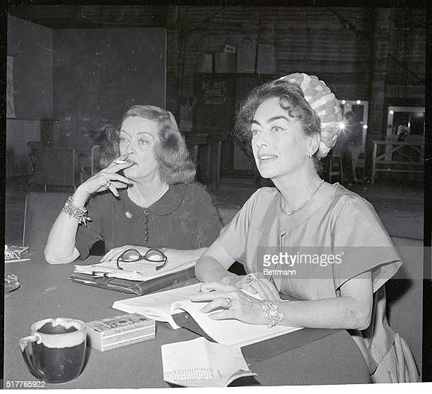 Bette Davis and Joan Crawford Hollywood's long reigning queens are photographed for the first time together as they look over the script of the film...