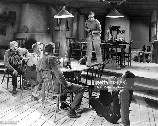 Bette Davis and other actors in a Western movie still sitting around a table in a home a man with a shotgun threatening the group a second man on the...