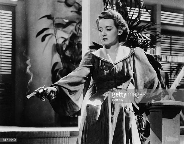 Bette Davis in the role of Leslie Crosbie fires a gun in a scene from 'The Letter' directed by William Wyler