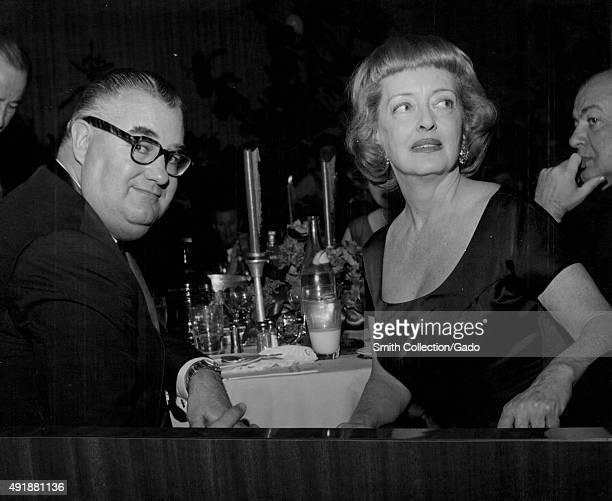 Bette Davis sitting at a banquet table with an unidentified man turning around in her chair and looking to her right in a dark room during a dinner...