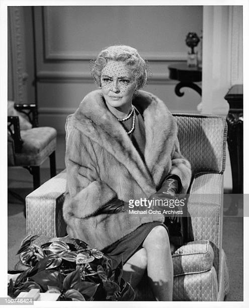 Bette Davis sitting in a chair wearing gloves a fur coat and a netted veil over her eyes in a scene from the film 'Where Love Has Gone' 1964