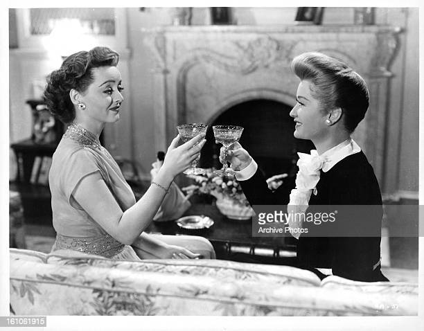 Bette Davis toasts with Miriam Hopkins in a scene from the film 'Old Acquaintance' 1943