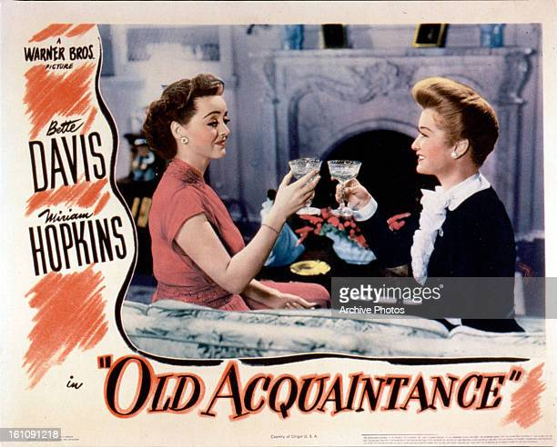 Bette Davis toasts with Miriam Hopkins in movie art for the film 'Old Acquaintance' 1943