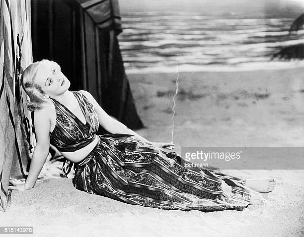 Bette Davis, young Warner Brothers actress, makes a very attractive beach comber when she wears the South Sea Island beach outfit in three pieces; a...