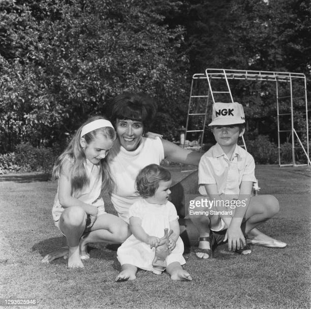 Bette Hill, the wife of British racing driver Graham Hill, with their children Brigitte and Samantha and son Damon , UK, 31st May 1966.
