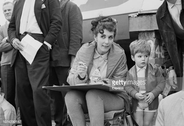 Bette Hill, wife of English Formula One racing driver Graham Hill, pictured timekeeping with her son Damon Hill during practice at Silverstone...