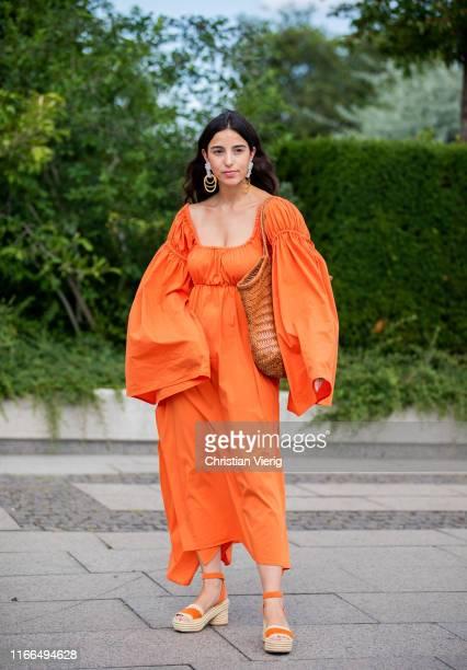 Bettina Looney is seen wearing orange dress with wide sleeves, bag outside Mykke Hofmann during Copenhagen Fashion Week Spring/Summer 2020 on August...