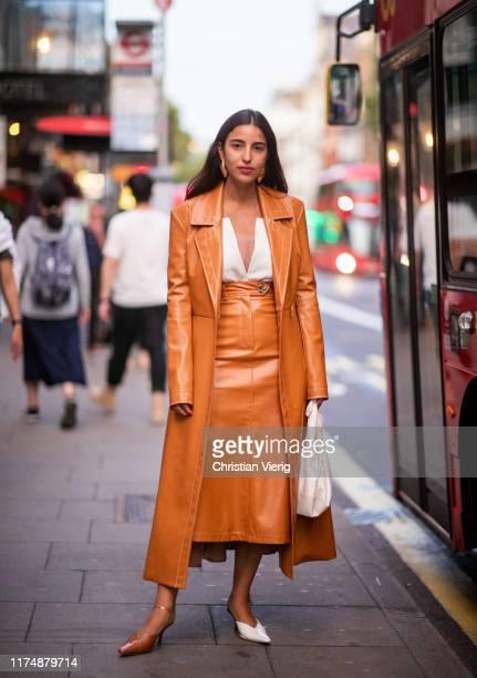 Bettina Looney is seen wearing orange skirt coat two tone white orange heels white bag outside AWAKE during London Fashion Week September 2019 on...