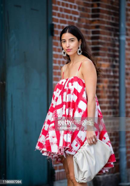 Bettina Looney is seen wearing red white dress, white clutch outside Rodebjer during Copenhagen Fashion Week Spring/Summer 2020 on August 07, 2019 in...