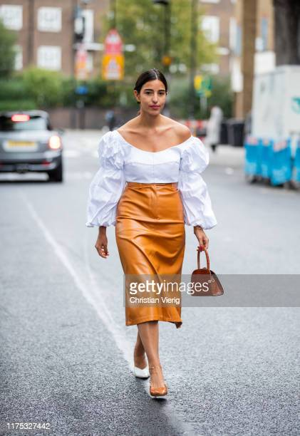 Bettina Looney is seen wearing white blouse with wide sleeves orange high waist skirt beige white two tone heels bag outside Christopher Kane during...