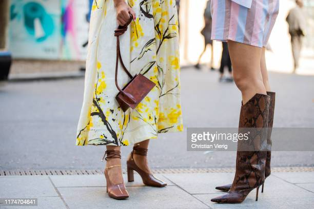 Bettina Looney is seen wearing yellow white dress with graphic print brown bag and Doina Ciobanu is seen wearing boots with snake print outside Ports...