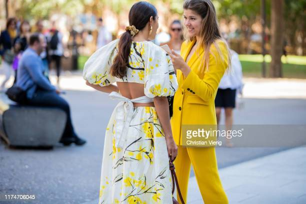 Bettina Looney is seen wearing yellow white dress with graphic print, brown bag and a guest wearing yellow suit outside Ports 1961 during London...