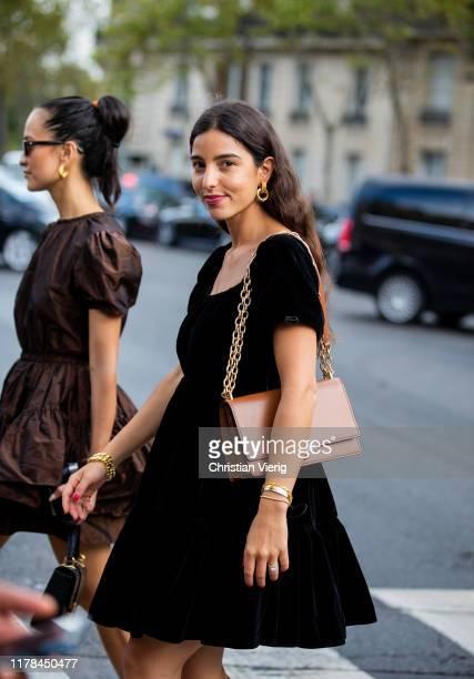 Bettina Looney seen wearing black velvet dress, brown bag outside Miu Miu during Paris Fashion Week Womenswear Spring Summer 2020 on October 01, 2019...
