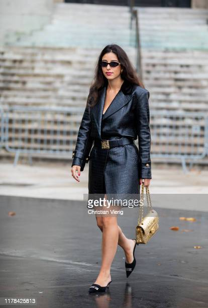 Bettina Looney wearing black belted leather dress, golden Chanel bag outside Chanel during Paris Fashion Week Womenswear Spring Summer 2020 on...