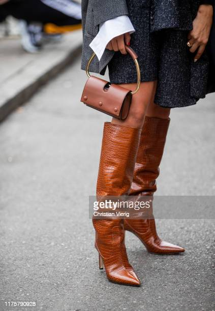 Bettina Looney wearing grey coat mini skirt bag brown boots outside the Max Mara show during Milan Fashion Week Spring/Summer 2020 on September 19...