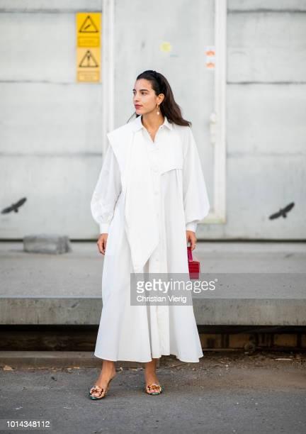 Bettina Looney wearing white dress red bag seen outside Ganni during the Copenhagen Fashion Week Spring/Summer 2019 on August 9 2018 in Copenhagen...
