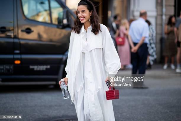 Bettina Looney wearing white dress red mini bag is seen outside Baum und Pferdgarten during the Copenhagen Fashion Week Spring/Summer 2019 on August...