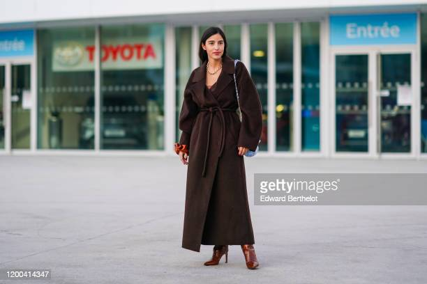 Bettina Looney wears a brown long coat, a blue Chanel bag, brown leather high heeled shoes, outside Jacquemus, during Paris Fashion Week - Menswear...