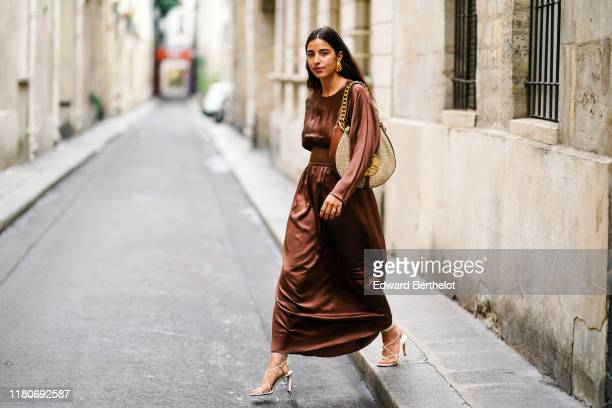 Bettina Looney wears a brown lustrous shiny dress a Loewe large bag heels shoes earrings outside Thom Browne during Paris Fashion Week Womenswear...