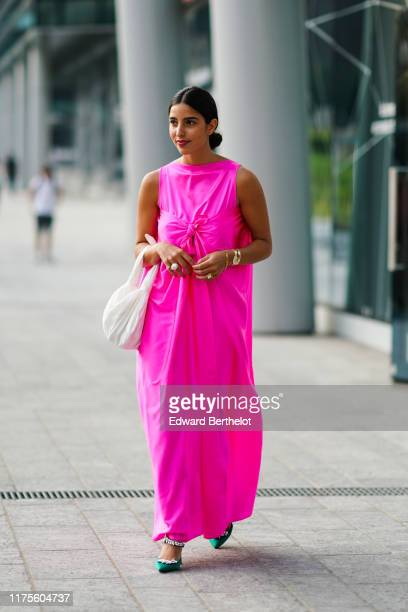 Bettina Looney wears a neon pink sleeveless dress a white bag outside the Alberta Ferretti show during Milan Fashion Week Spring/Summer 2020 on...
