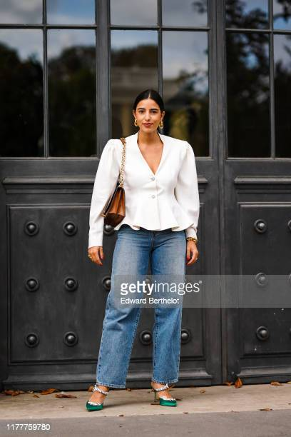 Bettina Looney wears a white ruffled jacket blue large jeans green shoes a brown bag outside Elie Saab during Paris Fashion Week Womenswear Spring...