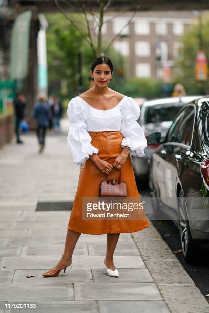Bettina Looney wears a white ruffled lace top with puff sleeves a tan color leather skirt a bag shoes during London Fashion Week September 2019 on...