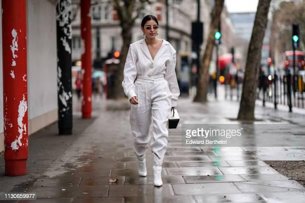 Bettina Looney wears a white striped jacket pants a rigid bag white boots sunglasses earrings during London Fashion Week February 2019 on February 18...