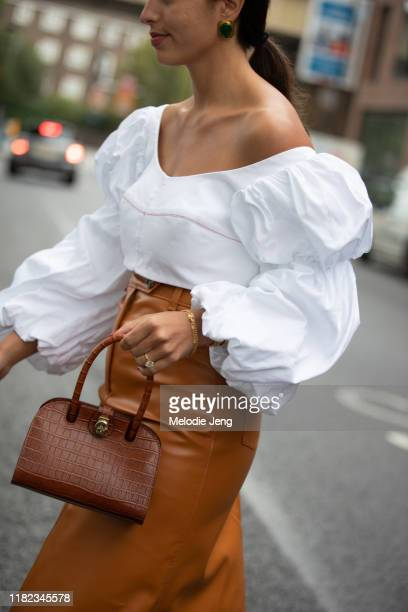 Bettina Looney wears an off-shoulder white Ellergy top, camel leather A.W.A.K.E. MODE skirt, and brown Manu Atelier lather bag at the Christopher...