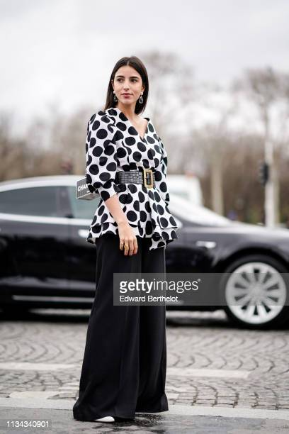 Bettina Looney wears crystal earrings a white Vneck top with large black dots and ruffled bottom edges a large black crocodile pattern belt with a...