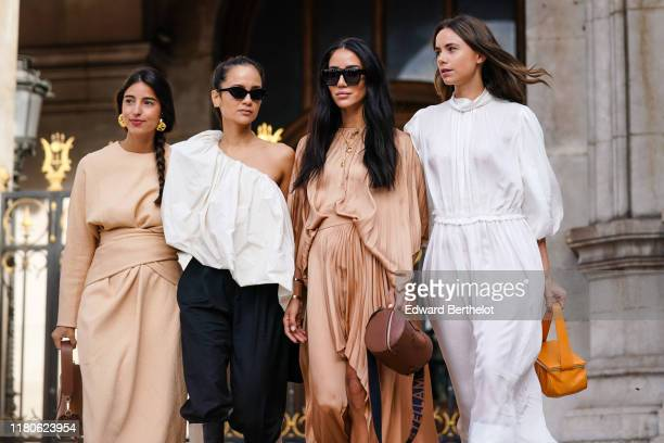 Bettina Looney wears earrings, a beige dress, a brown bag ; Anna Rosa Vitiello wears sunglasses, a gathered flowing asymmetric one-shoulder white...